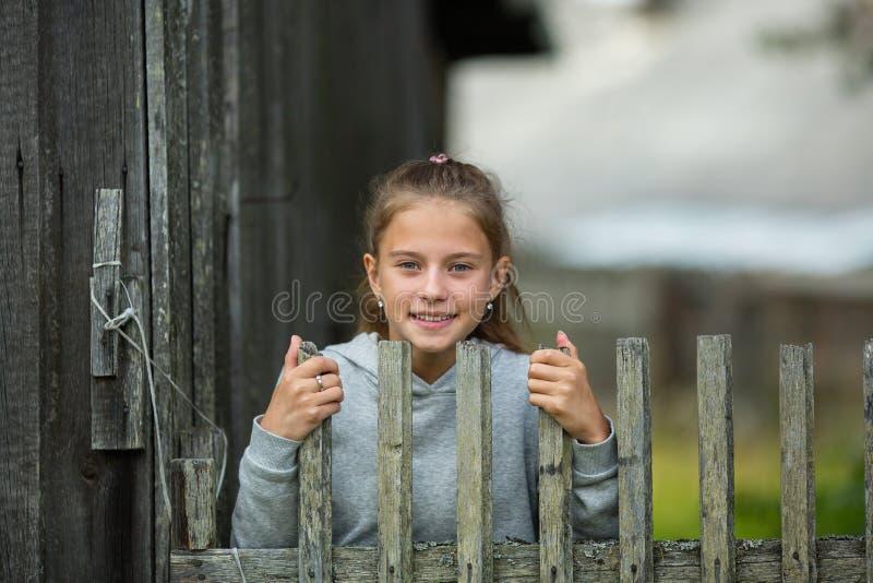 Liten gullig flicka nära ett trästaket i bygden arkivbilder