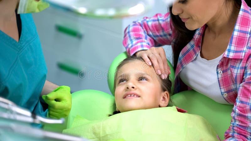 Liten gullig flicka på tandläkaren, vanlig undersökning av tänder, pediatrisk stomatology royaltyfri bild