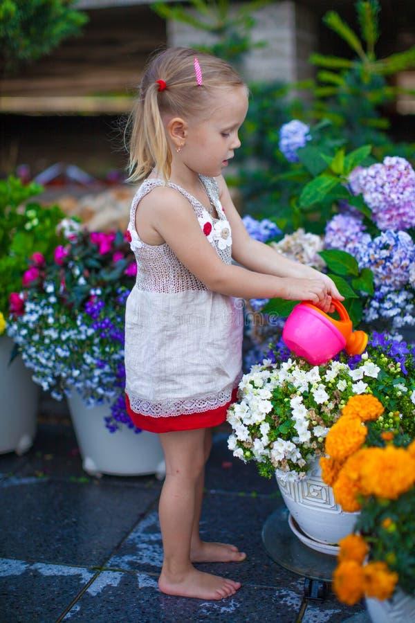 Liten gullig flicka som bevattnar blommor med bevattna royaltyfri fotografi