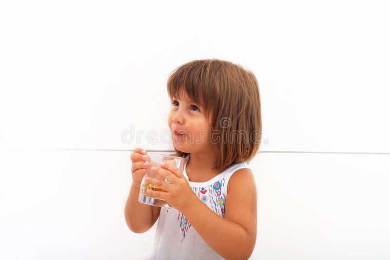Liten gullig flicka som dricker äppelmust från exponeringsglaset arkivfoto