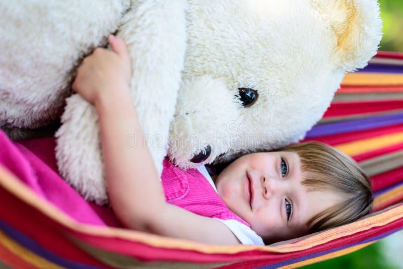 Liten gullig flicka som ligger på hängmattan med den stora nallebjörnen royaltyfria foton