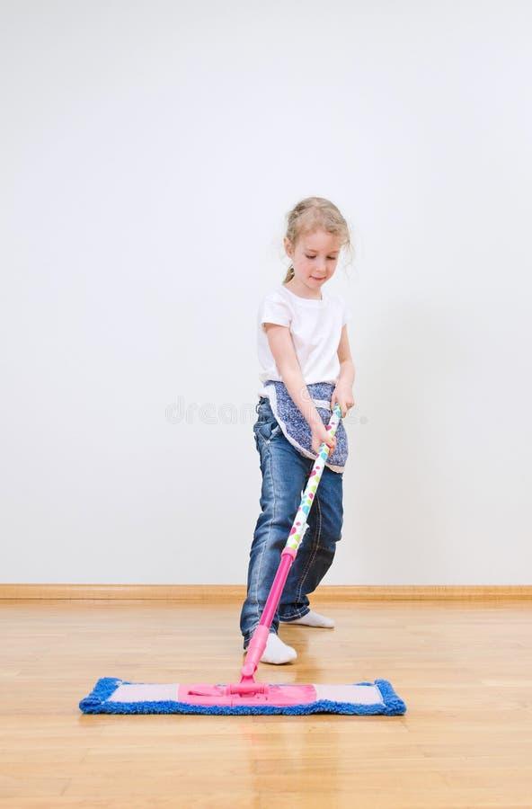 Liten gullig flicka som moppar golvet royaltyfri bild