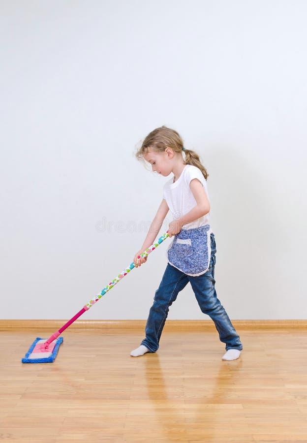 Liten gullig flicka som moppar golvet royaltyfri fotografi