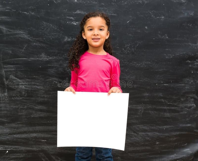 Liten gullig flicka som rymmer ett tomt pappers- ark arkivbilder