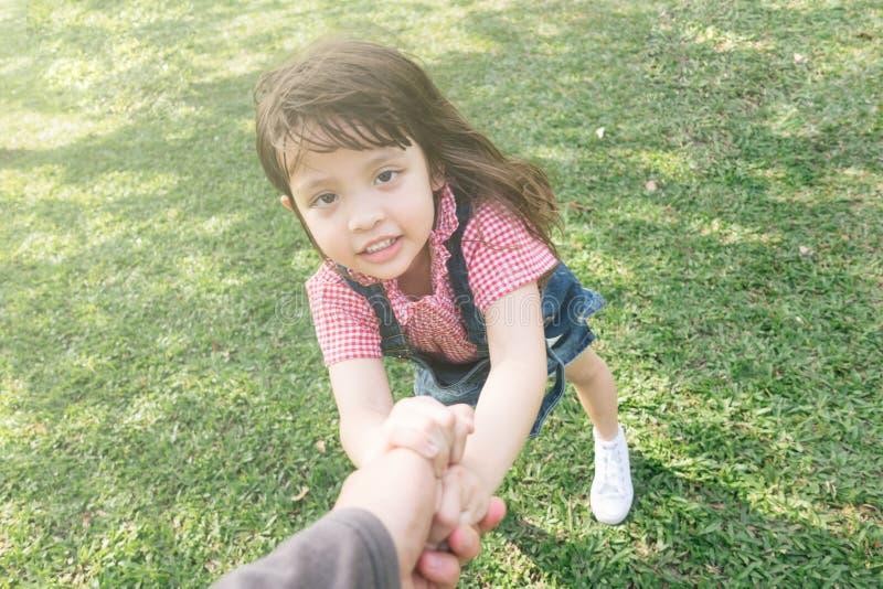 Liten gullig flicka som rymmer handföräldrar royaltyfria foton