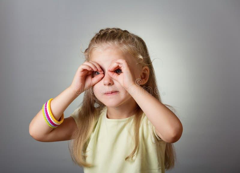 Liten gullig flicka som ser till och med kikare från hans fingrar på grå färger arkivfoto