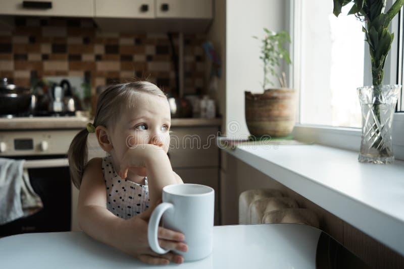 Liten gullig flicka som sitter på tabellen i köket fotografering för bildbyråer