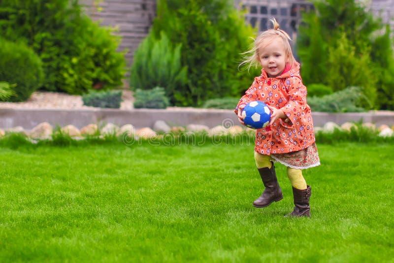 Liten gullig flicka som spelar bollen i gården royaltyfri foto