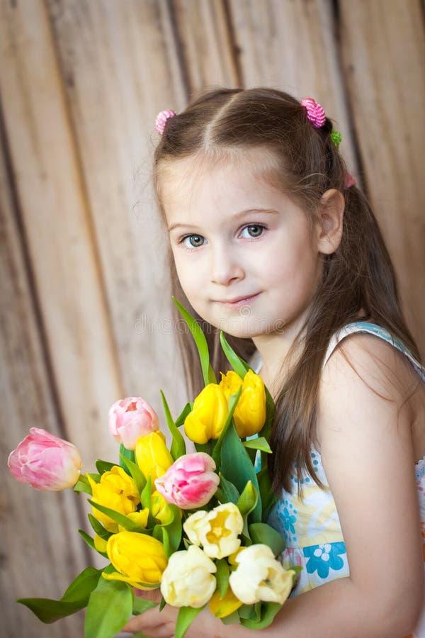 Liten gullig flickainnehavbukett av tulpan arkivbild