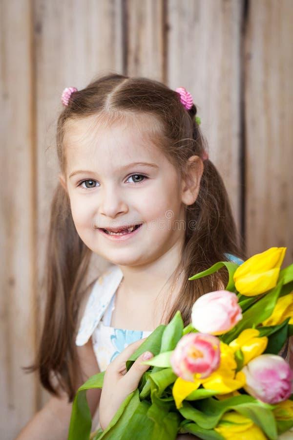 Liten gullig flickainnehavbukett av tulpan arkivbilder