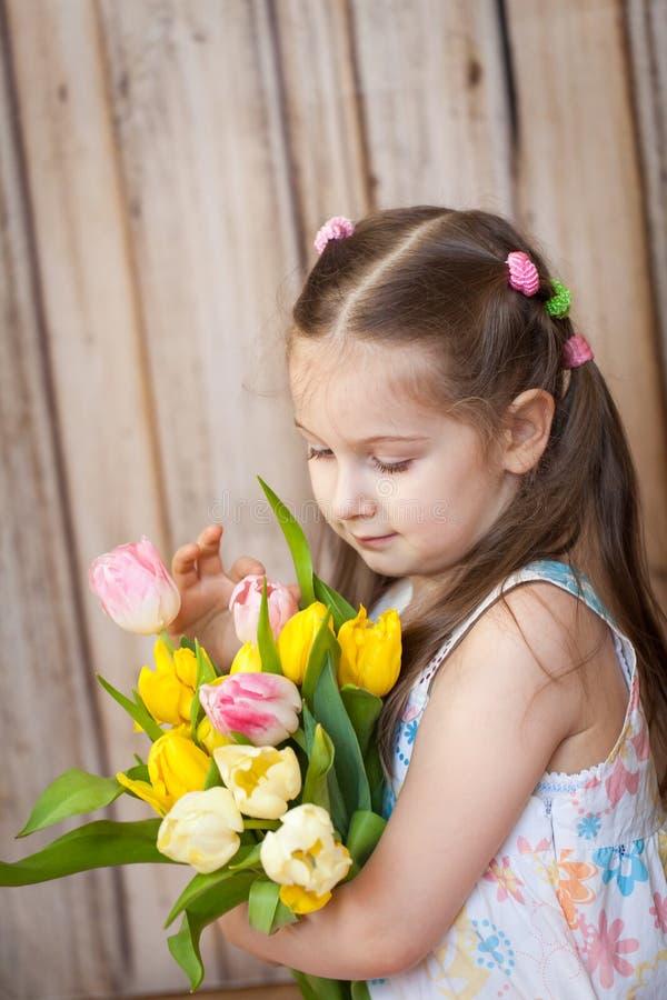 Liten gullig flickainnehavbukett av tulpan royaltyfri bild