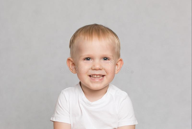 Liten gullig litet barnpojke som provocatively skrattar på vit bakgrund royaltyfri bild