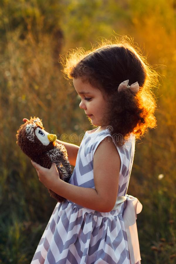 Liten gullig lockig flickahugd en fluffig leksakuggla Litet barnflickalek med den söta dockan Ett härligt solljus, värme färger H royaltyfri foto