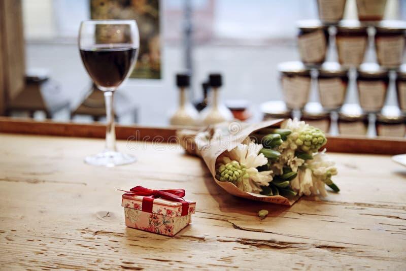 Liten gullig närvarande ask med pilbågen på trätabellen, blommor och exponeringsglas av vin bakom Romantiskt möte i kafé Dag c fö arkivfoton