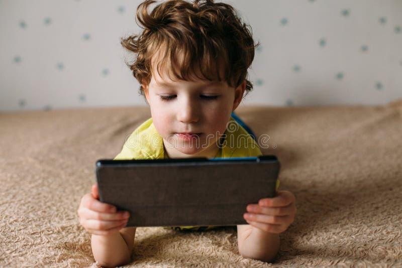 Liten gullig pojke i en grön T-tröja som spelar lekar på en minnestavla och håller ögonen på tecknade filmer Litet barn med minne royaltyfri fotografi