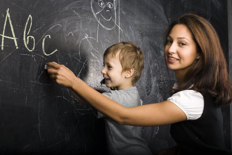 Liten gullig pojke med den unga läraren i klassrum som studerar på att le för svart tavla arkivbild