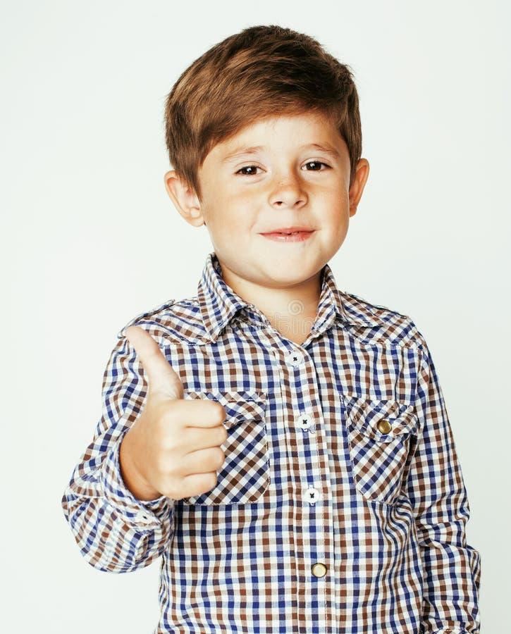 Liten gullig pojke på vita bakgrundsgesttumbs som ler upp closeupen, livsstilfolkbegrepp arkivfoton