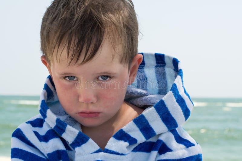 Liten gullig ungemen och trutat, svikit Härlig liten unge med atopic dermatit på bakgrunden av havet, arkivfoto