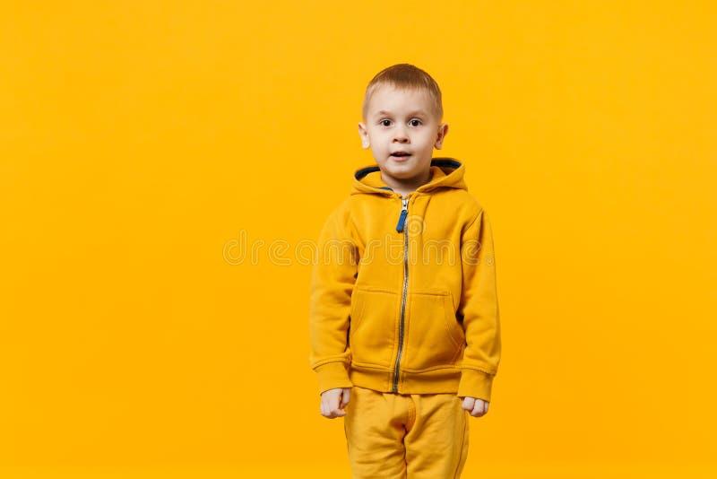 Liten gullig ungepojke 3-4 år gammal bärande gul kläder som isoleras på ljus orange väggbakgrund, barnstudio royaltyfri foto