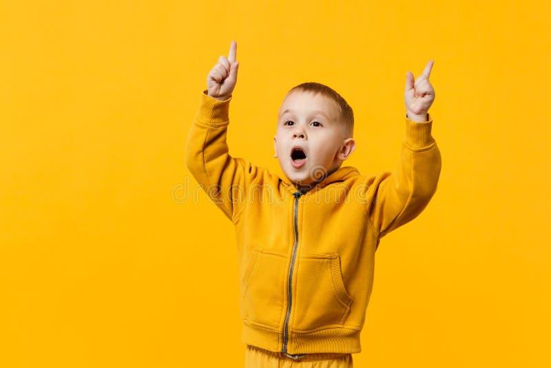 Liten gullig ungepojke 3-4 år gammal bärande gul kläder som isoleras på ljus orange väggbakgrund, barnstudio royaltyfri fotografi