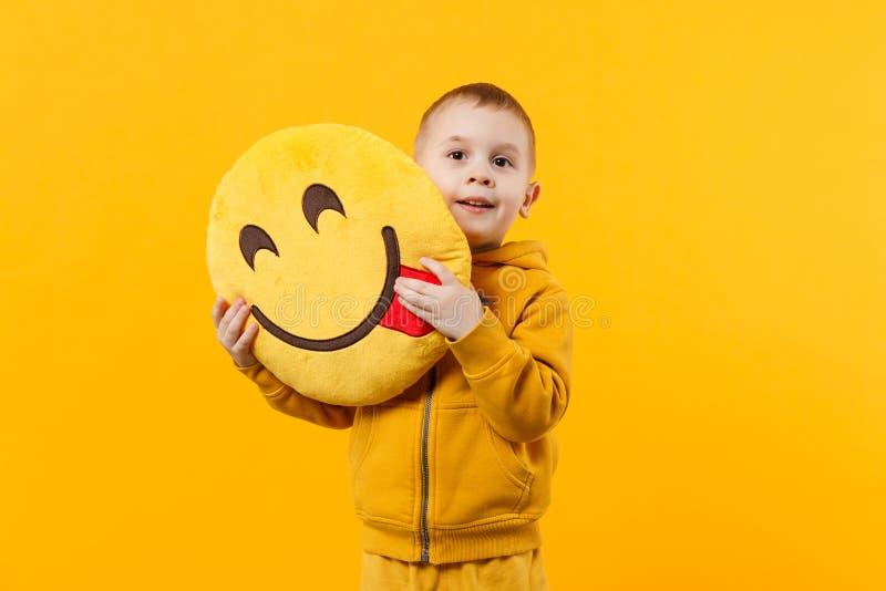 Liten gullig ungepojke 3-4 år gammal bärande gul kläder som isoleras på ljus orange väggbakgrund, barnstudio royaltyfri bild