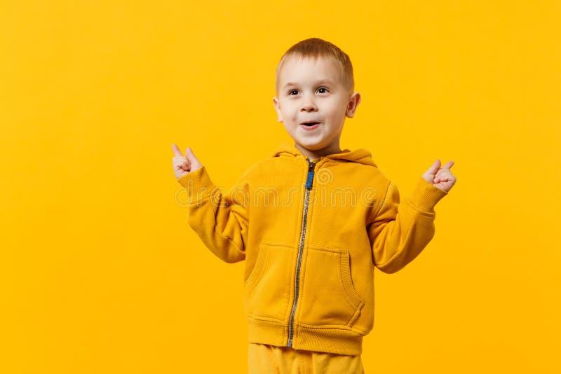 Liten gullig ungepojke 3-4 år gammal bärande gul kläder som isoleras på ljus orange väggbakgrund, barnstudio royaltyfria bilder