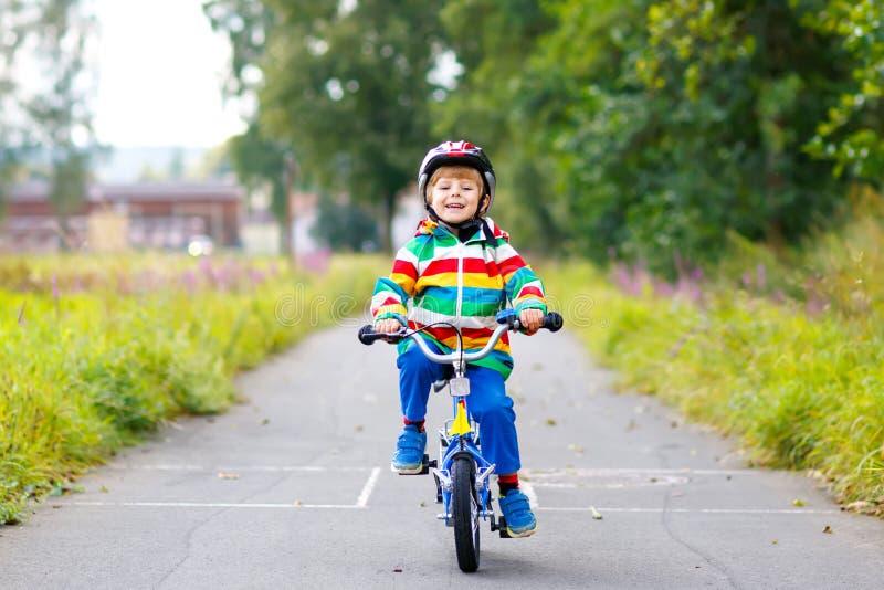 Liten gullig ungepojke på cykeln på sommar eller autmndag Sunt lyckligt barn som har gyckel med att cykla på cykeln arkivfoto