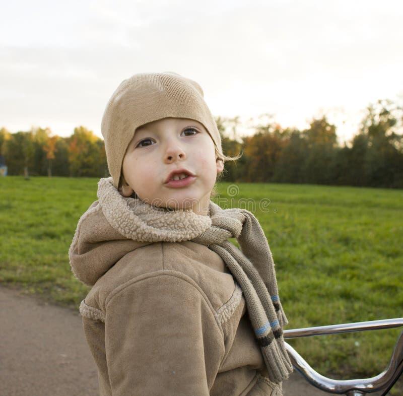 Liten gullig verklig pojke på emotionellt le slut för cykel upp yttersida i grönt nöjesfält arkivfoto