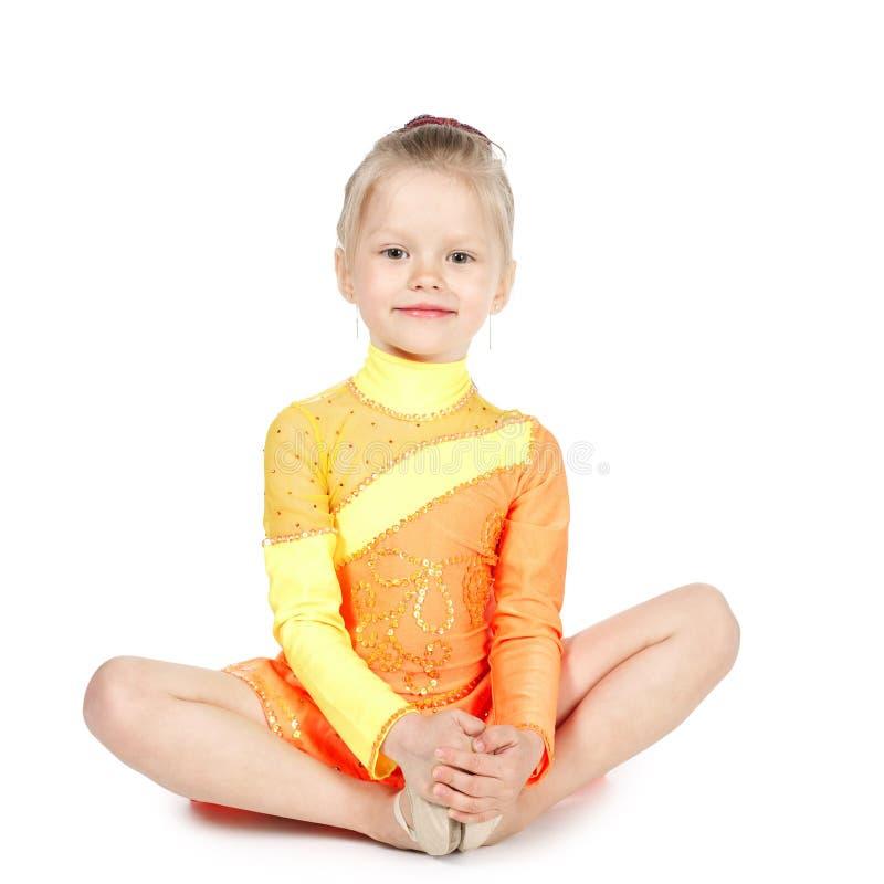 Liten gymnastflicka på vit bakgrund arkivfoton