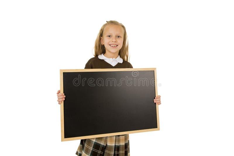 Liten härlig blond skolflicka som ler det lyckliga och gladlynta innehavet och den lilla tomma svart tavla för visning royaltyfria bilder