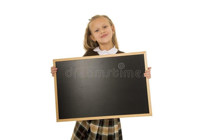 Liten härlig blond skolflicka som ler det lyckliga och gladlynta innehavet och den lilla tomma svart tavla för visning arkivfoton