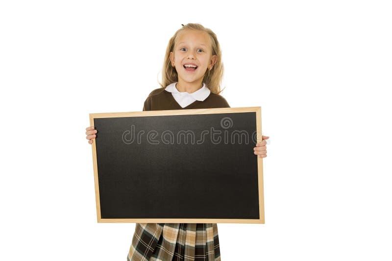 Liten härlig blond skolflicka som ler det lyckliga och gladlynta innehavet och den lilla tomma svart tavla för visning arkivbild