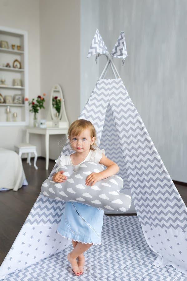 Liten härlig flicka med kuddeanseende i tipi på barnkammarerum fotografering för bildbyråer