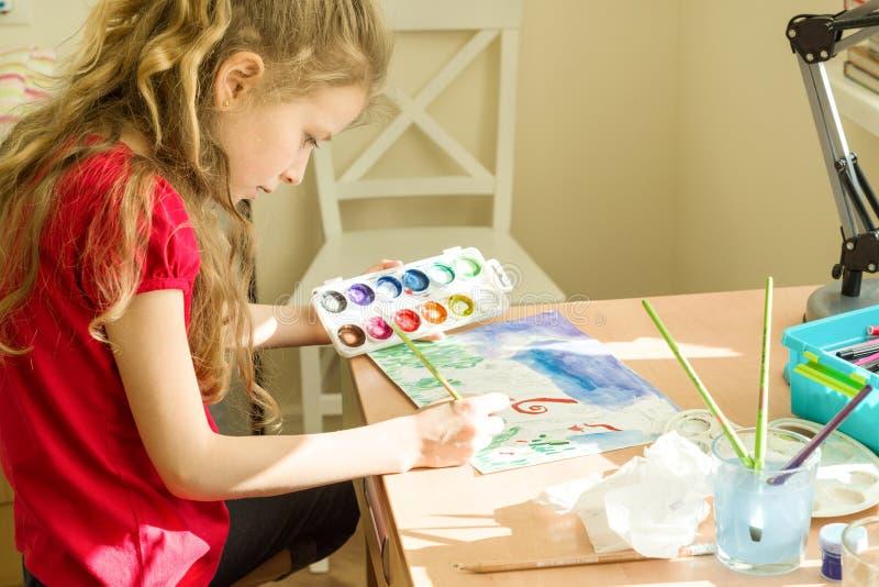 Liten härlig flickamålning med vattenfärger som hemma sitter på tabellen Barnkreativitet, rekreation, utveckling arkivfoton