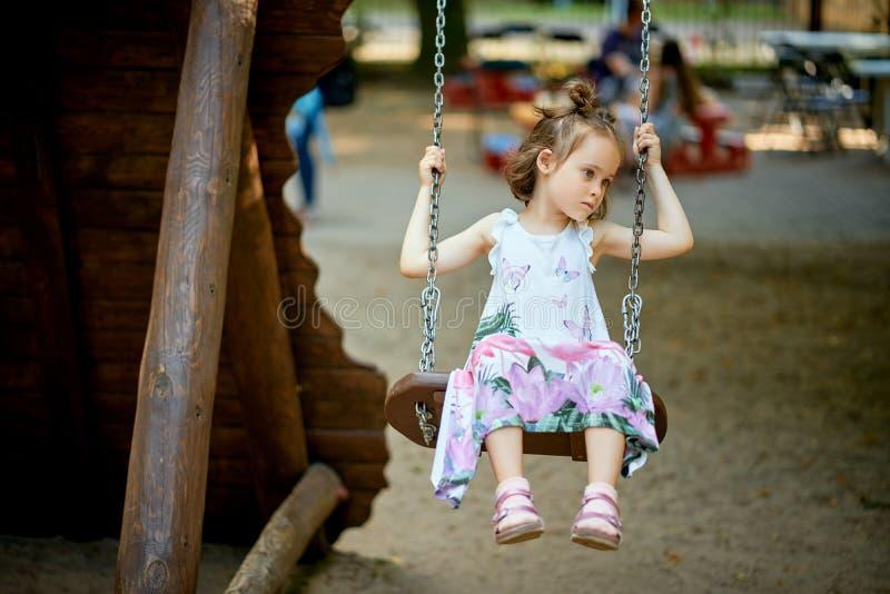 Liten härlig ledsen flicka på gunga med den eftertänksamma framsidan på lekplatsen arkivbilder