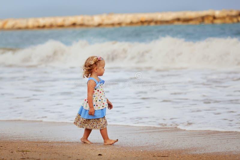 Liten härlig lycklig flicka som går på stranden royaltyfri bild