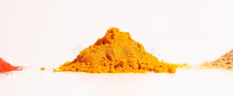 Liten hög av kryddor, gurkmejapulvret, korianderpulvret och rött chilipulver arkivbilder