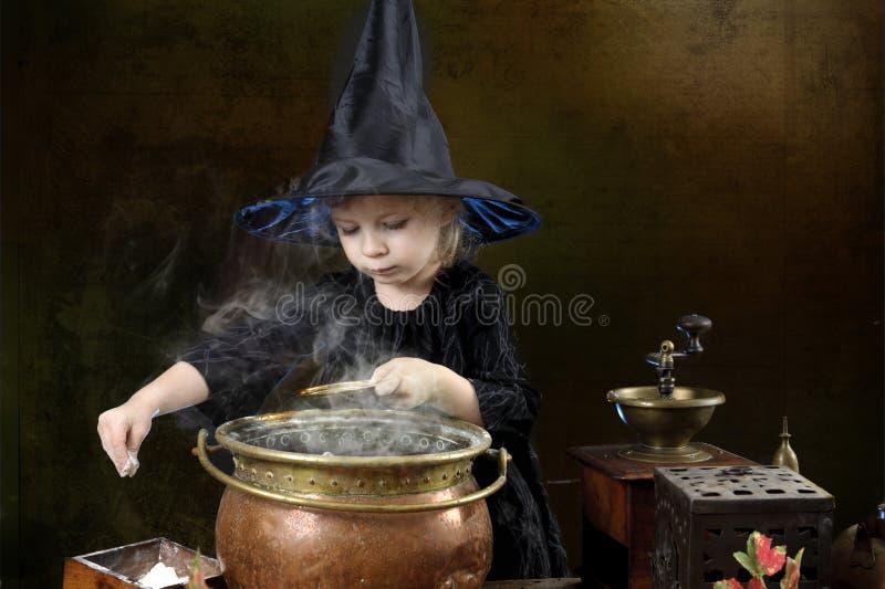 Liten halloween häxa med kitteln royaltyfri fotografi