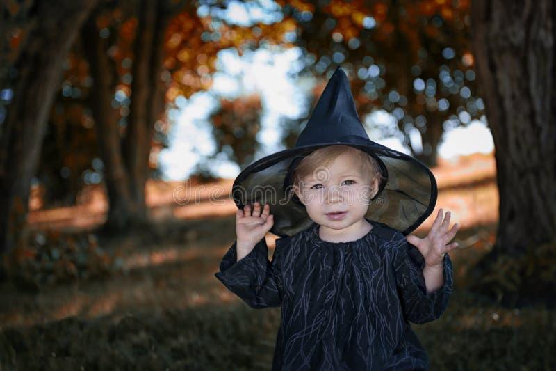 Liten halloween häxa utomhus med kitteln royaltyfri foto