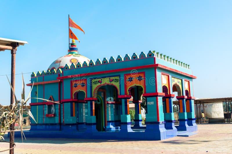 Liten hinduisk tempel med carvings i livliga blått och reds som skjutas i gujarat Indien royaltyfria foton