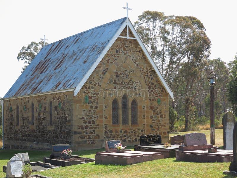 Liten historisk kyrka med kyrkogården royaltyfria bilder