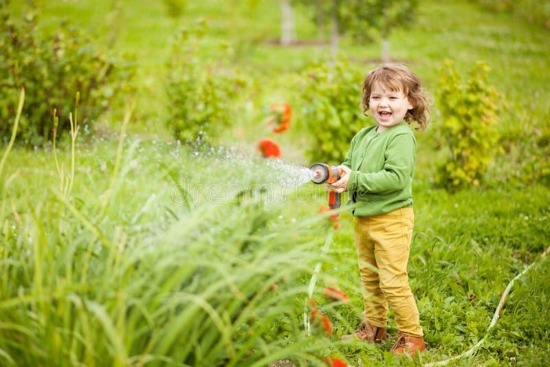 Liten hjälpreda för mödrar som bevattnar trädgården och har gyckel royaltyfria bilder