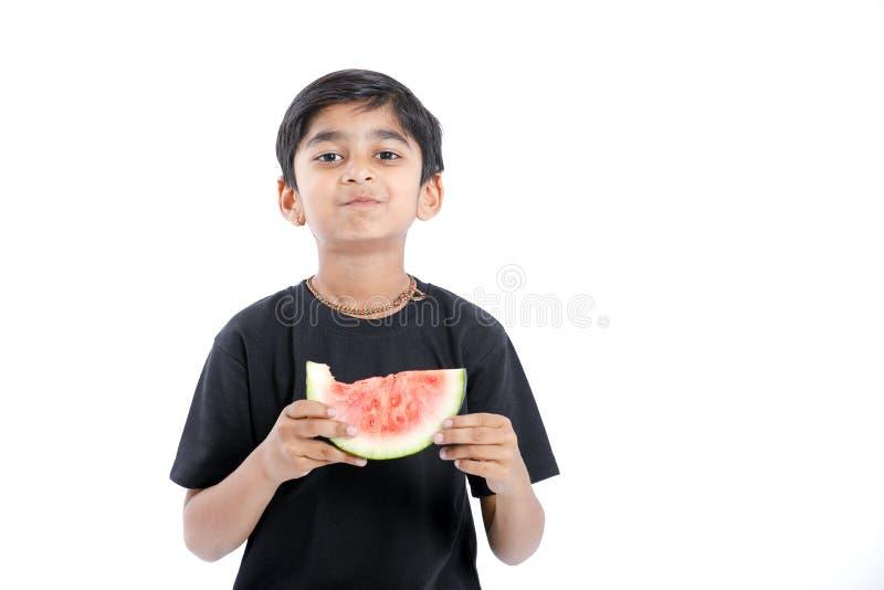 liten indisk pojke som äter vattenmelon med åtskilliga uttryck arkivbild
