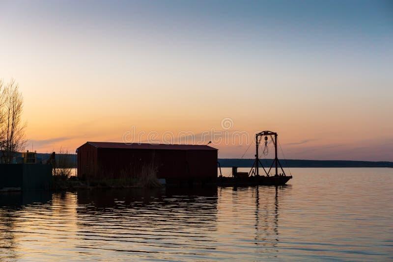 Liten industriell pir på floden efter solnedgången, härligt vattenlandskap, lugn arkivbild