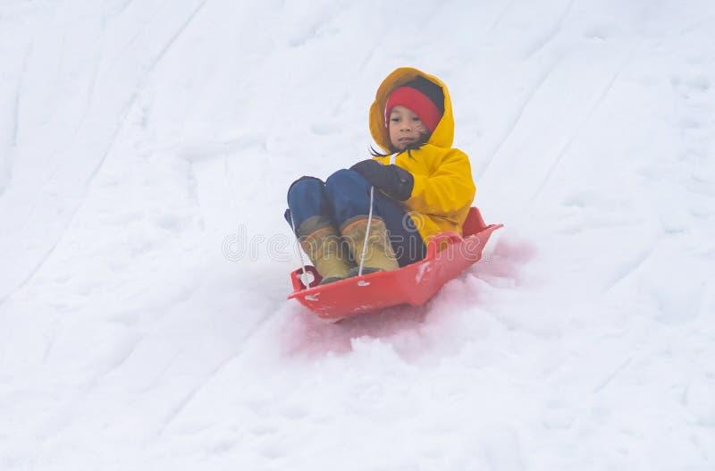 Liten japansk flicka som glider ner sn?sl?den i den Gala Yuzawa Ski semesterorten arkivbild