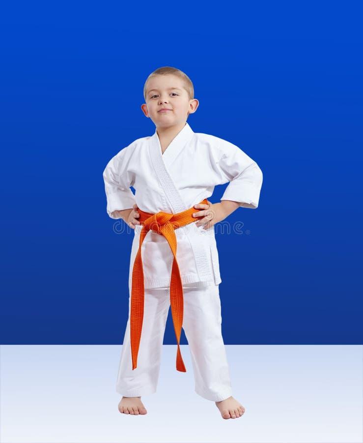 Liten karateka med det orange bältet på en blå bakgrund royaltyfria bilder