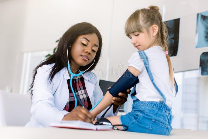Liten kaukasisk flicka på barnläkarkontor som mäter blodtryck Ung afrikansk doktor som mäter blod arkivfoton