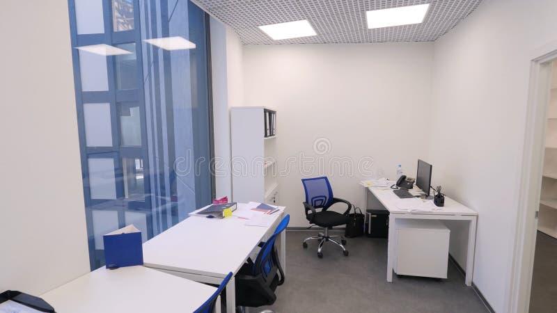 Liten kontorssikt Icke-arbete tid i regeringsställning Modern kompakt kontorsrum med flera arbetsstationer och ljust royaltyfria foton