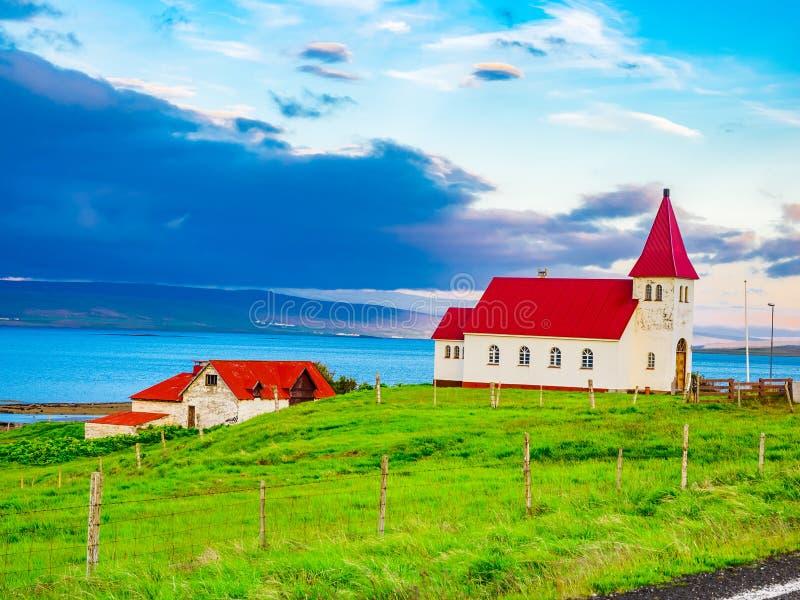 Liten kyrka på fält för grönt gräs på sjösidan royaltyfri bild