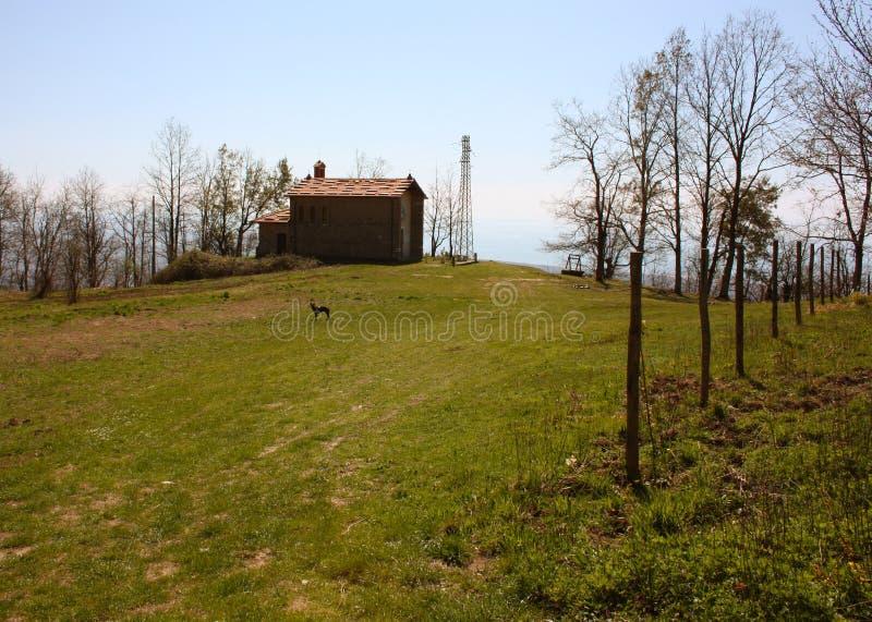 Liten kyrka som överges, i obruklighet, på de Apuan fjällängarna av den Tuscan Apenninesen i en röjning på en solig vårdag royaltyfria bilder